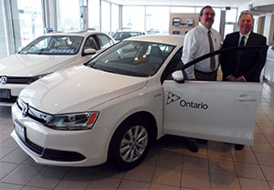 Mike Cole, Government of Ontario, with Bruce Lindsay, Volkswagen Canada at Richmond Motors of Chatham, where the delivery took place