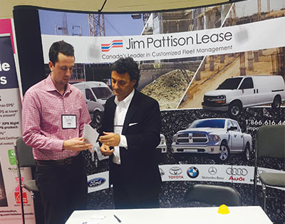 Tyler Simpson, Owens Corning confers with Lou Mancini, Jim Pattison Lease at the Jim Pattison Lease display