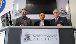(From left) Matt Rispin, Frank Panza, and Stu Ralph, North Toronto Auction, celebrate 10 years, on the auction block.